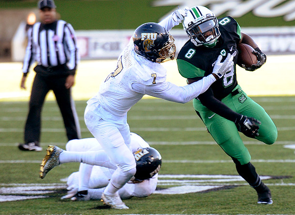 Rick Barbero/The Register-Herald<br /> Remi Watson, right, of Marshall, breaks away from Jeremiah McKinnon, of FIU, during game at Joan C. Edwards Stadium in Huntington Saturday evening.