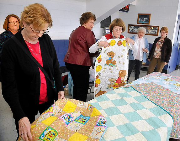 Brad Davis/The Register-Herald<br /> Quilters from the Sew Sew Sisters and Hands All Around organize and divide up several special baby quilts before being donated to Raleigh General Hospital and Birthright of Beckley Wednesday afternoon at the Beckley-Raleigh County Convention Center. At left looking over a quilt is Mary Ann Eccles while acting chair of the Appalachian Treasures Quilt Show Judith Bragg (2nd from left) and Hands All Around quilter Nancy Cameron (third from left holding quilt) sort quilts.