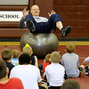 Brad Davis/The Register-Herald<br /> Young area wrestlers of all ages pay attention as former Pittsburgh Steelers offensive lineman and strength coach John Kolb demontrates proper technique for maintaining a strong center of gravity during the Fellowship of Christian Athletes' third annual Mountain State Wrestling Clinic Saturday morning at Woodrow Wilson High School.