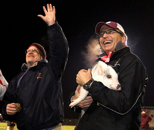 Brad Davis/The Register-Herald<br /> Dr. Gary Polins, left, waves to the Van Meter Stadium crowd after smooching Owen the pig, held by Principal Ron Cantley, right, after he raised the most money for Woodrow Wilson's project graduation Friday night.
