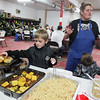Brad Davis/The Register-Herald<br /> Seven-year-old Justin Cadle, left, grabs a roll while Rhodell Volunteer Fire Department chief Patricia Cox, right, shoots the breeze with fellow community members (unphotographed behind camera) during the town's annual Thanksgiving dinner Saturday night.