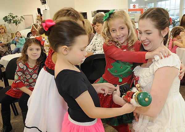 Rick Barbero/The Register-Herald<br /> Jenna Meador, as Clara, right, gets a hug from Camryn Harris as other childen gather around to look at the nutcracker in her hands during the Sugar Plum Fairy Tea Party was held at Lewis Automotive Group, on 100 Appalachian Dr in Beckley Sunday afternoon. Guest enjoyed tea with Clara, the Sugar Plum Fairy and other characters from The Nutcracker. The characters also performed ballet from the show. This was a benefit event for the Heather Zickefoose Scholarship fund to aid talented students to be professional dancers.