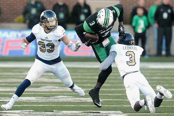 Rick Barbero/The Register-Herald<br /> Davonte Allen, center, of Marshall, geta tackled by Collin Olsen, left and Richard Leonard, of FIU during game at Joan C. Edwards Stadium in Huntington Saturday evening.