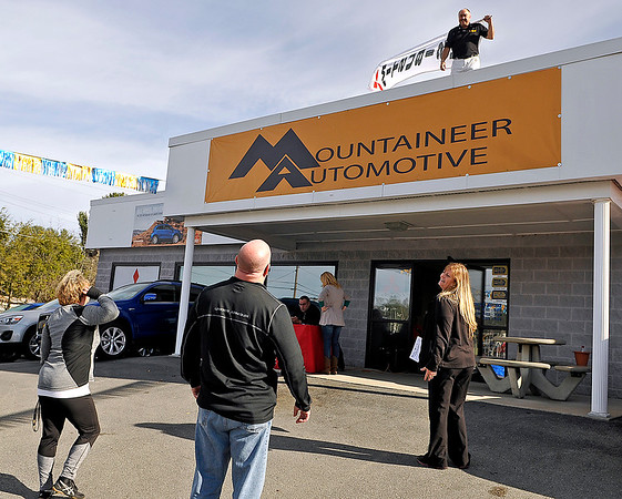 """Brad Davis/The Register-Herald<br /> Princeton residents Teresa (far left) and Chris Spears (middle) notice enthusiastic sales manager Darrell Blackburn hanging out on the roof during what was called a """"bike-a-thon"""" Friday afternoon at Mountaineer Mitsubishi as sales rep Jeanie Cole, right, leads them inside to purchase a vehicle. The Eisenhower Drive dealership teamed up with the Beckley Board of Realtors and WJLS 99.5 FM for the event, which solicited donations of toys and coats along with bikes for the upcoming Mac's Toy Fund throughout the day with the goal of filling up an entire box truck with donations. Blackburn, for his part, wouldn't come down from the roof until that happened. He spent the day atop the building waving Mitsubishi flags, occasionally howling like a dog and wearing different costumes, which included a turkey, ninja and even a cheerleader. Mountaineer also donated a bike themselves for every vehicle sold yesterday."""