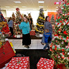 Brad Davis/The Register-Herald<br /> Oak Hill residents Tabitha Armstrong (left, pointing) gets a kick out of some of the Christmas trees available as she and family members Betty Armstrong and three-year-old Austin Hoover make their way through the Wonderland of Trees charity auction event Friday night inside the Crossroads Mall.