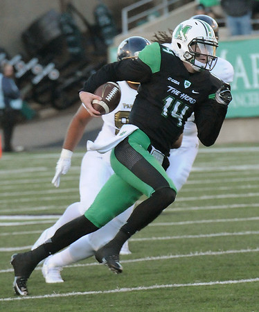 Rick Barbero/The Register-Herald<br /> Chase Litton, of Marshall, breaks away ffor some extra yarage against FIU during game at Joan C. Edwards Stadium in Huntington Saturday evening.