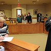 Rick Barbero/The Register-Herald<br /> Tracie Ella Claypool, left, signs some paperwork after Raleigh County Circuit Judge Robert Burnside swore her in as the new adult drug court probation officer Monday morning.