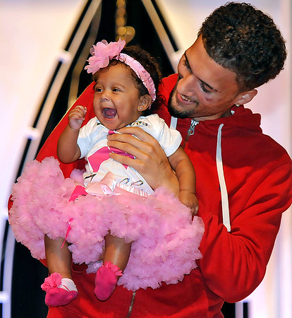 Brad Davis/The Register-Herald<br /> Little Zoee Lacy is carried across the stage by her dad during the 7th annual Pretty in Pink Pageant Sunday afternoon in the Woodrow Wilson High School auditorium, a fundraising event for the Susan G. Komen Foundation and Newspapers in Education.
