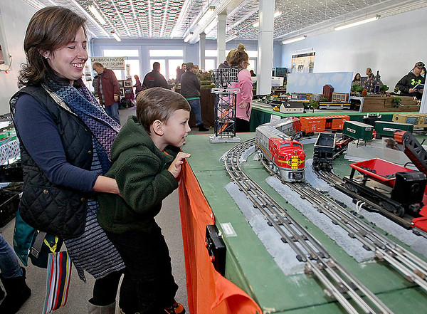 Brad Davis/The Register-Herald<br /> Four-year-old train enthusiast and Charlottesville, Va. resident Owen Cyphers gets a closer look with the help of his mother Annette as a model train chugs by during Hinton's Historic Railroad Days festival Sunday afternoon inside the city's railroad museum. Cyphers couldn't be pried away from the interactive model railroad setup, built by Scott Depot resident Terry Eades, which featured different stations where cars could load up with coal or other items at the push of a button. It also had the famous Sante Fe engines, his favorite.