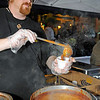 Brad Davis/The Register-Herald<br /> Fosters cook Jason Tilley prepares a sample during this year's Chili Night event Saturday evening.