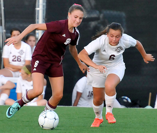 Brad Davis/The Register-Herald<br /> George Washington defender Riley Lohan overcomes the pursuit of Woodrow Wilson's Rachel Quattrone during the Flying Eagles' loss to the Patriots Thursday evening at the YMCA Paul Cline Memorial Sports Complex.