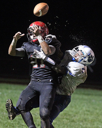 Brad Davis/The Register-Herald<br /> Liberty receiver Brandon Lemon has the ball knocked loose as Princeton defensive back Je'Nye Hearn hits him as it arrives during a soggy contest with the Tigers Friday night in Glen Daniel.