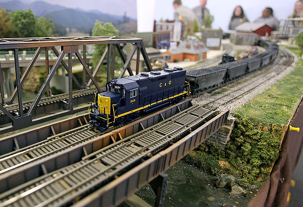 Brad Davis/The Register-Herald<br /> A model C & O coal train chatters its way along a model bridge within its elaborate model community, created and assembled by Kanawha United Model Railroaders member Ron Blessing (not photographed), during Hinton's Historic Railroad Days festival Sunday afternoon inside the town's railroad museum.