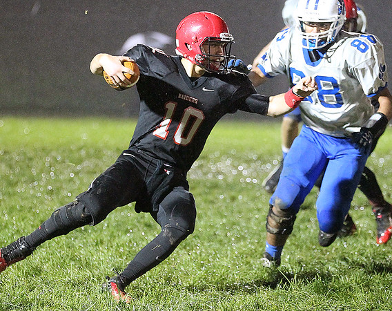 Brad Davis/The Register-Herald<br /> Liberty quarterback Hunter Wright tries to cut up the field as he escapes pressure from Princeton's Mohommad Abdelwahed (#88) during a soggy contest with the Tigers Friday night in Glen Daniel.
