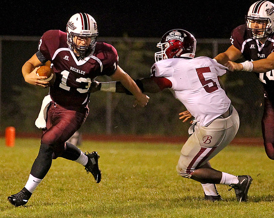 Brad Davis/The Register-Herald<br /> Woodrow Wilson's Sutton Radford tries to escape the clutches of Bluefield's Jason Edwards Friday night at Van Meter Stadium.