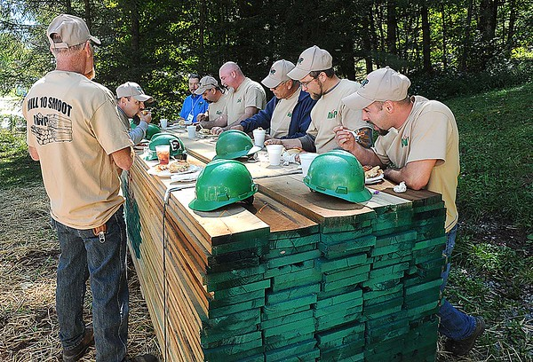 Rick Barbero/The Register-Herald<br /> Workers for Allegheny Wood Products in Smoot eating lunch on a pile of wood during a dedication ceremony held at the plant Monday morning.