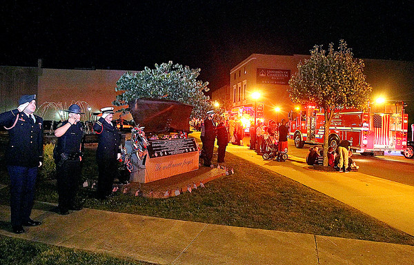 Brad Davis/The Register-Herald<br /> First responders, military and police salute at left as the annual parade of lights rolls past the September 11th memorial at Word Park along Neville Street Friday night.