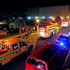 Brad Davis/The Register-Herald<br /> Fire trucks and other first response vehicles make their way past the September 11th Memorial along Neville Street during the Parade of Lights Friday night.