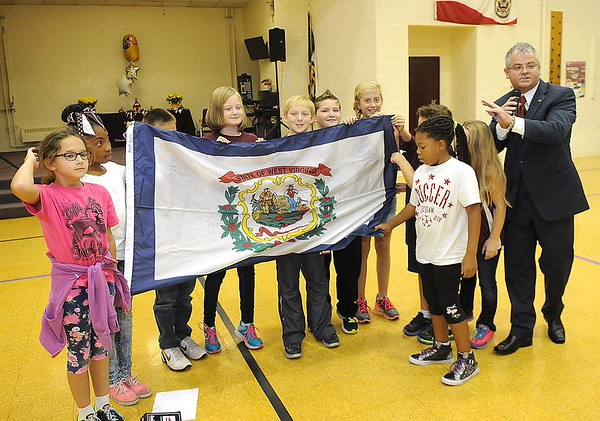 Rick Barbero/The Register-Herald<br /> Student Council holds up a State flag that was presented by Delegate Mick Bates, right, during Crescent Elementary School on Crescent Road in Beckley celebration for being named one of the best schools in the state. Crescent was only one of nine out of seven hundred elementary schools in WV to receive the School of Excellence award.