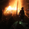 Brad Davis/The Register-Herald<br /> Beckley firefighters keep unextinguishable flames at bay Friday night after a large fire broke out in a storage yard behind the Lewis Ritchie Apartments. A building at the apartment complex was damaged by intense heat but the fire never spread to it thanks to BFD's efforts.