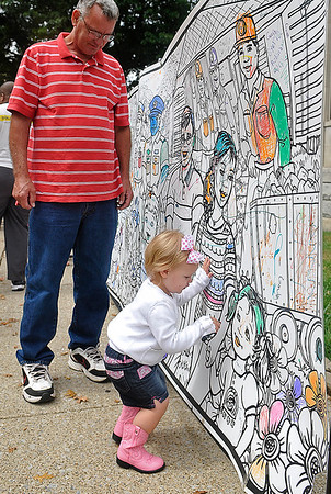Brad Davis/The Register-Herald<br /> Two-year-old Madison Scites adds some color to the giant coloring wall on Main Street as her grandfather Paul looks on during the Kids Classic Festival Saturday afternoon.