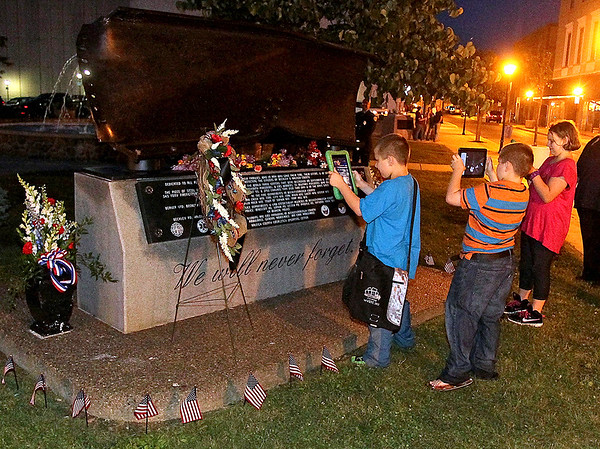 Brad Davis/The Register-Herald<br /> Beckley youngsters Aneesa Demoss (right), 11, and 9-year-old twin brothers Julian (middle) and Tayshawn Escott take in a bit of a history lesson as they film and photograph Word Park's September 11th memorial with their tablets prior to annual Parade of Lights Friday night in downtown Beckley.