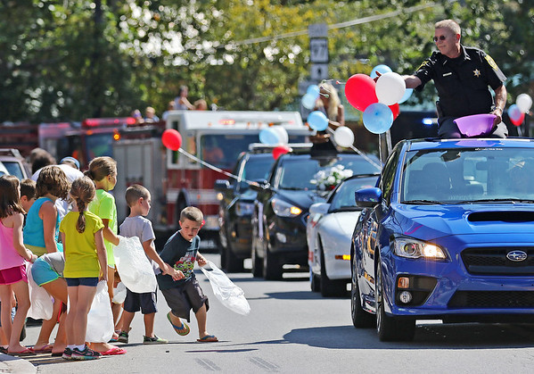 Chris Jackson/The Register-Herald<br /> Children race to pick up candy thrown by Wyoming County Sheriff Randall Aliff during theannual Labor Day parade and carnival om Pineville on Monday.