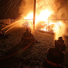Brad Davis/The Register-Herald<br /> Beckley firefighters keep unextinguishable flames at bay Friday night after a large fire broke out in a storage yard behind the Lewis Ritchie Apartments. A building at the apartment complex was damaged by intense heat but the fire never spread thanks to BFD's efforts.