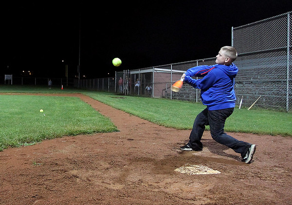 Brad Davis/The Register-Herald<br /> Nine-year-old Cole Cunningham crushes a pitch into the night sky during the Kids Classic Home Run Derby Saturday night at the Beckley Little League Fields.