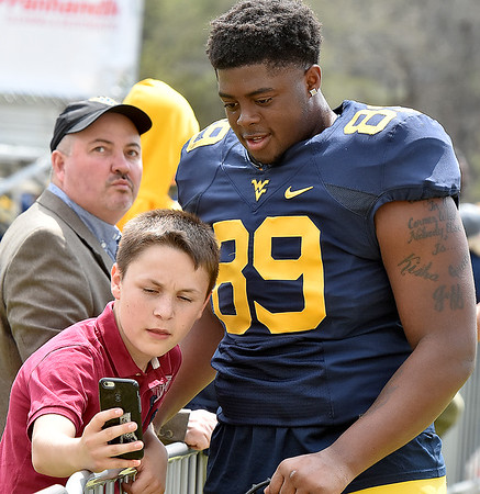 (Brad Davis/The Register-Herald) West Virginia Defensive lineman Jeffery Pooler gets a selfie with a young fan following the Mountaineers' Gold-Blue Spring football game Saturday afternoon at The Greenbrier.