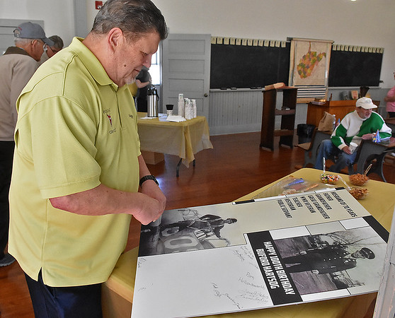 (Brad Davis/The Register-Herald) Mark Lilly, one of Buford Hartsog's former students, looks over an honorary poster after signing it during his 100th birthday celebration inside the school house on the Youth Museum/Exhibition Coal Mine grounds Saturday afternoon.