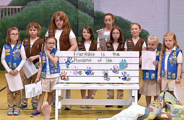 (Brad Davis/The Register-Herald) Girl Scouts from Troop 51264 unviel what's called a buddy bench Wednesday afternoon at Cranberry-Prosperity Elementary School. The bench, which was a community service project for the young scouts, will be placed on Cranberry-Prosperity's playground, where kids with no playmates during recess can meet and make new friends.
