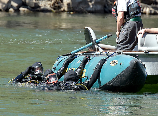 Search and rescue divers move into position to begin looking for the missing victim of a fishing boat accident on the New River near Prince Thursday afternoon.