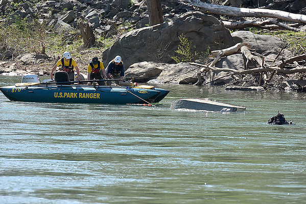 Search and rescue workers pull a fishing boat from the New River as divers (seen at right) search for a missing victim near Prince Thursday afternoon. The small boat capsized with two aboard shortly after launching from a park about a mile from the Pugh memorial bridge.