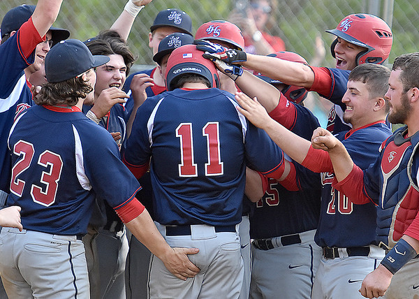 (Brad Davis/The Register-Herald) Teammates mob Independence's Cody Green (#11) at home plate after blasting a third inning grand slam against Summers County Wednesday evening in Hinton.