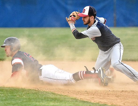 (Brad Davis/The Register-Herald) Independence's Ryan Brandstetter, left, looks up at the umpire's safe call through a cloud of dust as Bluefield shortstop Devon Goins is late with the tag during the second inning of the Patriots' game against the Beavers Wednesday evening in Coal City. Brandstetter legged out a double on the play after his high blooper to shallow right fell just out of reach of Bluefield second baseman Dominick Buzzo.