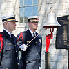 Beckley firefighter Brian Williams rings the bell as Robert Donelow looks on during the annual Upper Big Branch Memorial at the Raleigh County Courthouse in downtown Beckley on Tuesday. (Chris Jackson/The Register-Herald)