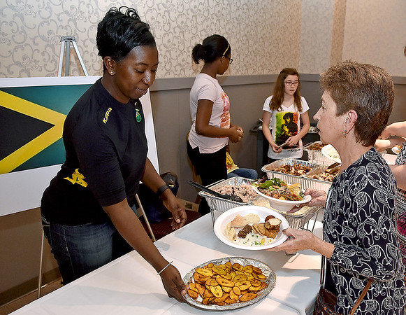 (Brad Davis/The Register-Herald) Georgianna Richards, left, chats with attendees as she serves up homemade Jamaican food during the YMCA International Dinner Sunday afternoon at the Beckley-Raleigh County Convention Center.