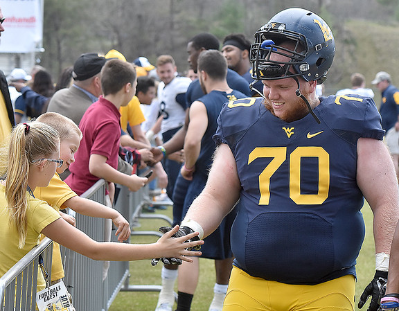 (Brad Davis/The Register-Herald) West Virginia Defensive lineman D.J. Carozza, a Parkersburg native, smiles as he gets high fives from a couple of young fans following the Mountaineers' Gold-Blue Spring football game Saturday afternoon at The Greenbrier.