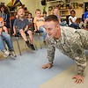 Wesley Bowling, Army National Guard Specialist, demostrates to students at Lester Elementary School about some of his physical training he does for the Guard during the schools Career Day. Students rotated every 10 minutes and listened to nine vendors speak about their careers.<br /> (Rick Barbero/The Register-Herald)