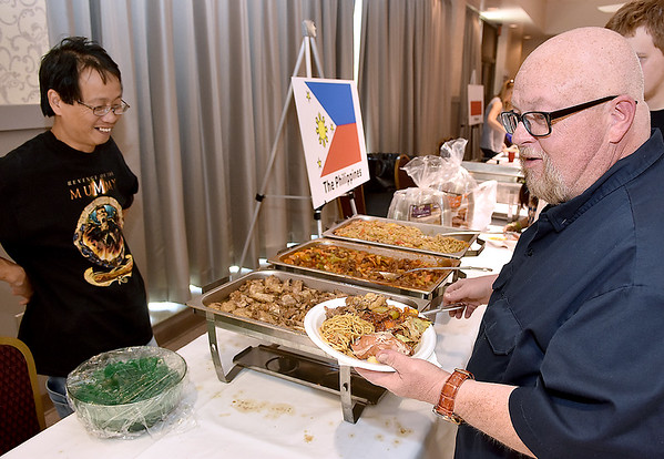 (Brad Davis/The Register-Herald) Rick Rizer, right, tries some Philipino food as Felino Carunungan (left), whose wife Dulce made all the food, looks on during the YMCA International Dinner Sunday afternoon at the Beckley-Raleigh County Convention Center.