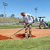 "John Ball, center from Beckley, works on scattering baseball mix on the infield of one of the little league fields in Beckley as Adam Bond, of Beckley, drives a tractor to fill up on more on Monday. The two volunteer their working often 13-hour days to get the fields ready for opening day this weekend, Ball said. ""I played out here 27-years ago,"" Ball said stopping between racking the mixture of sand and clay. ""My little brother plays here. My dad played here. We just try and get it ready and look as nice as possible and get the kids a good place to play."" (Chris Jackson/The Register-Herald)"