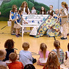 (Brad Davis/The Register-Herald) Students watch during an assembly as Girl Scouts from Troop 51264 unviel what's called a buddy bench Wednesday afternoon at Cranberry-Prosperity Elementary School. The bench, which was a community service project for the young scouts, will be placed on Cranberry-Prosperity's playground, where kids with no playmates during recess can meet and make new friends.