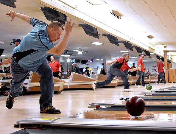 (Brad Davis/The Register-Herald) Bowler Adam Muntz, left, takes a turn for his team, the Fanelli Boys, as they and several other teams compete during the opening day of a weekend adult state bowling league April 3 at Leisure Lanes.