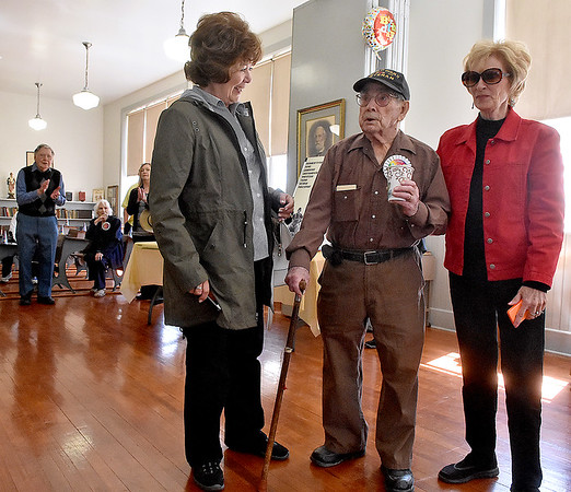 (Brad Davis/The Register-Herald) World War II veteran and former teacher Buford Hartsog is serenaded with the happy birthday song as he celebrates his 100th birthday inside the school house on the Youth Museum/Exhibition Coal Mine grounds Saturday afternoon. Standing with him are sister-in-laws Barbara, left, and Nancy Hodde, while younger brother Jarrell, background far left, and his wife Loretta, background seated, look on.