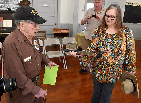 (Brad Davis/The Register-Herald) Hartsog's daughter Gina Bennett, right, brings out a relic from his teaching days which several of his former students remember, a wooden paddle bearing the names of some its most frequent recipients during his 100th birthday celebration inside the school house on the Youth Museum/Exhibition Coal Mine grounds Saturday afternoon.