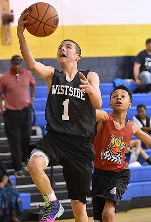 (Brad Davis/The Register-Herald) Westside's (Clear Fork) Daniel Reed, left, drives and scores against Team Crucial (Beckley) during a 8th grade matchup in the Spring Fling Tournament Sunday afternoon at Shady Spring High School. Team Crucial won the game 47-39.