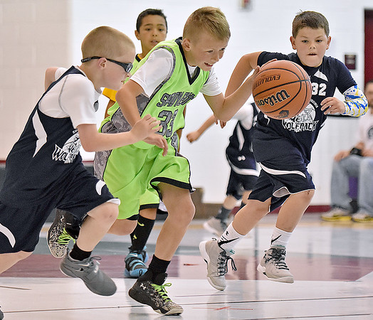 (Brad Davis/The Register-Herald) Shady Elite's Brady Rose, middle, rushes up the court as Southern West Virginia Wolfpack's Ashton Arthur, left, and Degan Williams try to run him down during a third grade division matchup in the Spring Fling Basketball Tournament Saturday afternoon at Daniels Elementary School.