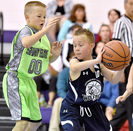(Brad Davis/The Register-Herald) Southern West Virginia Wolfpack's Brayden Hatfield, right, keeps the ball from Shady Elite's Jack Williams as he looks for an open teammate during a third grade division matchup in the Spring Fling Basketball Tournament Saturday afternoon at Daniels Elementary School.