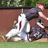 (Brad Davis/The Register-Herald) Woodrow Wilson third baseman Cameron Pack rolls over George Washington's Grant Wells, right, while trying to tag him out during the Flying Eagles' loss to the Patriots Friday afternoon in Beckley. Wells would be called safe on the play.